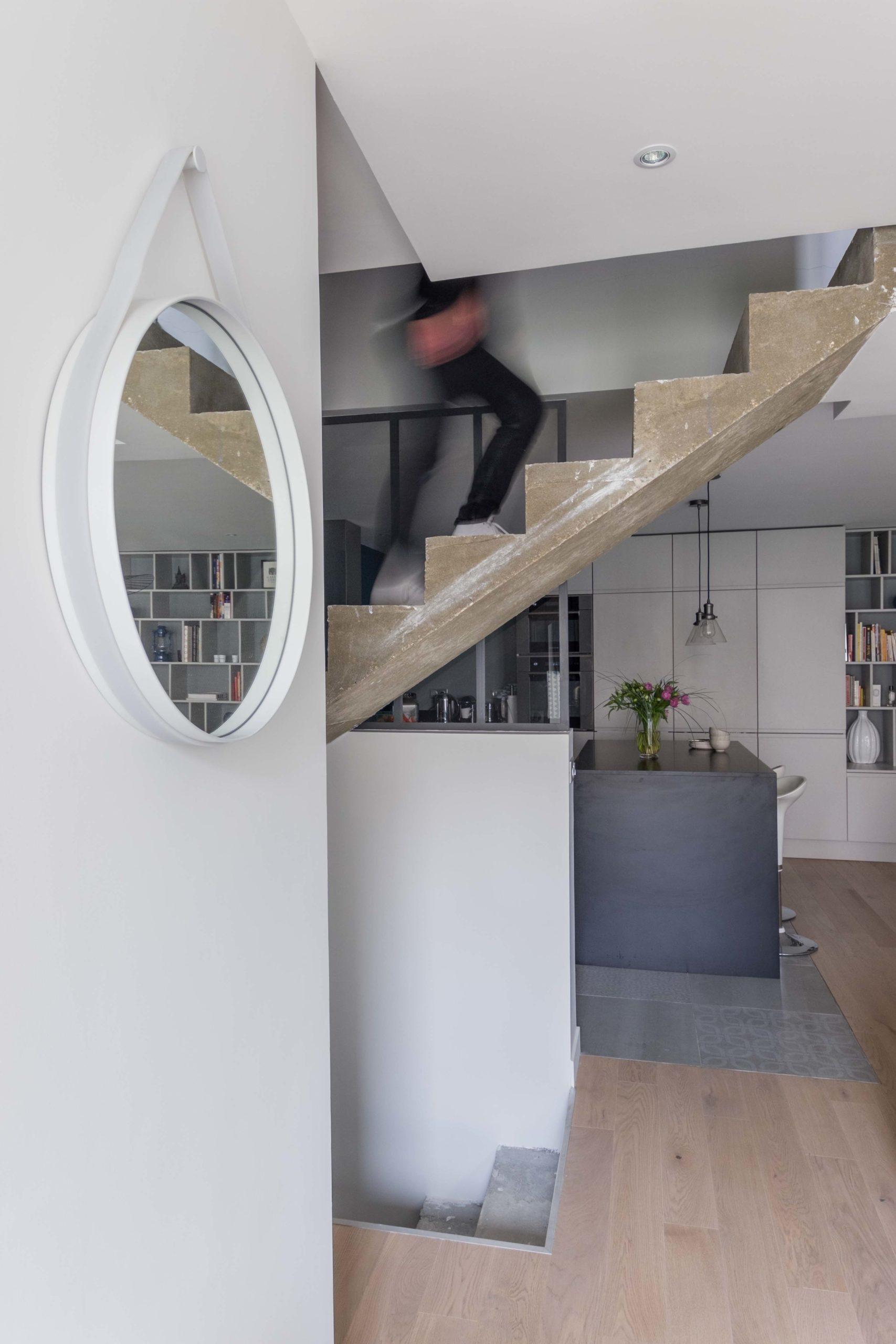 escalier béton avec vue sur cuisine ouverte avec ilot et bibliothèque