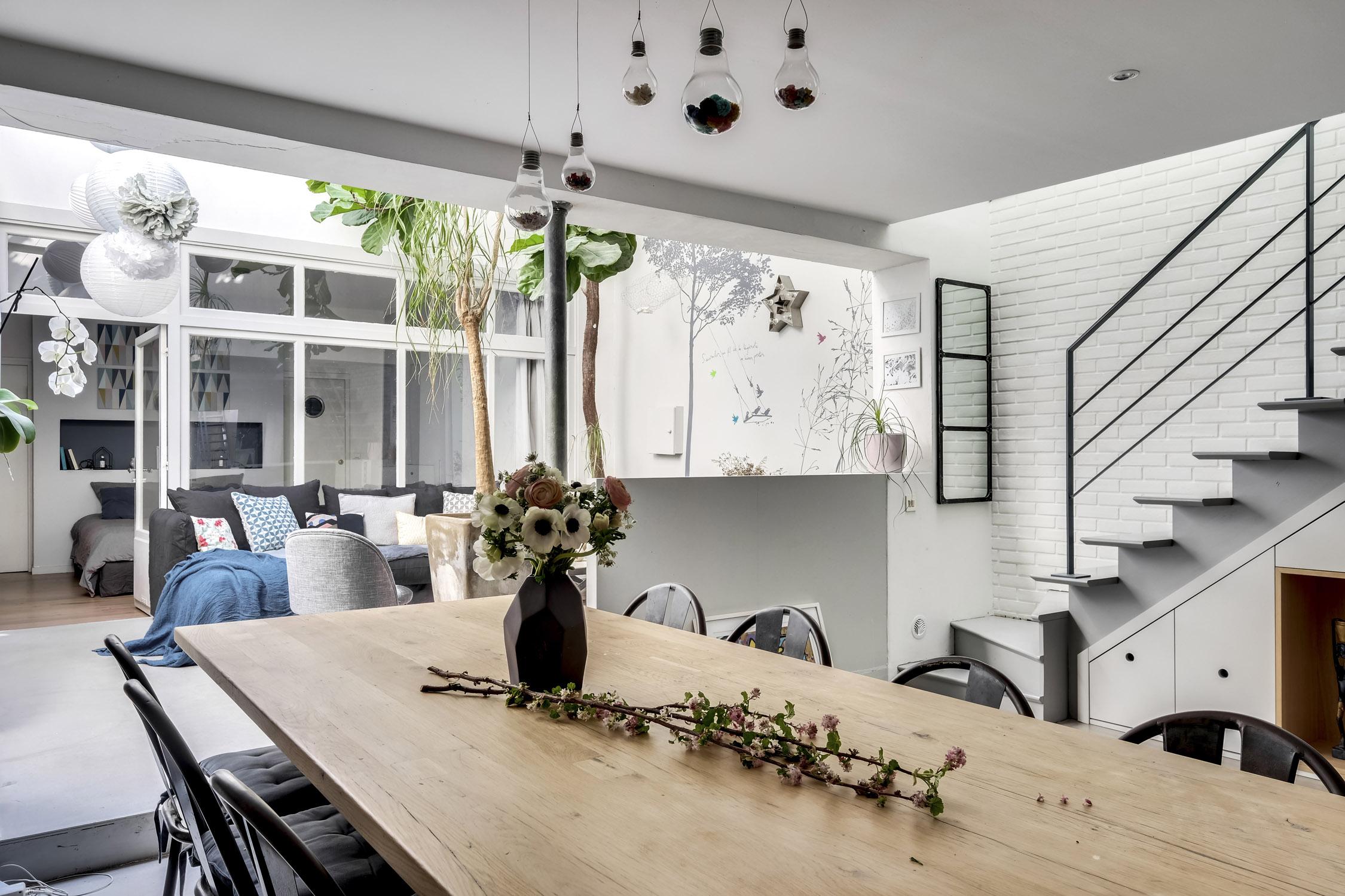 salle à manger avec table en chêne massif et vue sur le salon sous verrière et escaliers rénovation murs et merveilles