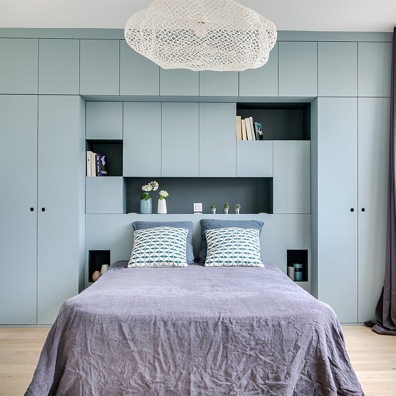 chambre avec dressing intégré tête de lit et niches ouvertes en bleu et gris avec une suspension nuage