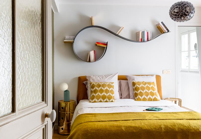 chambre parentale avec plaid et coussins couleur safran et étagère Kartell par murs et merveilles