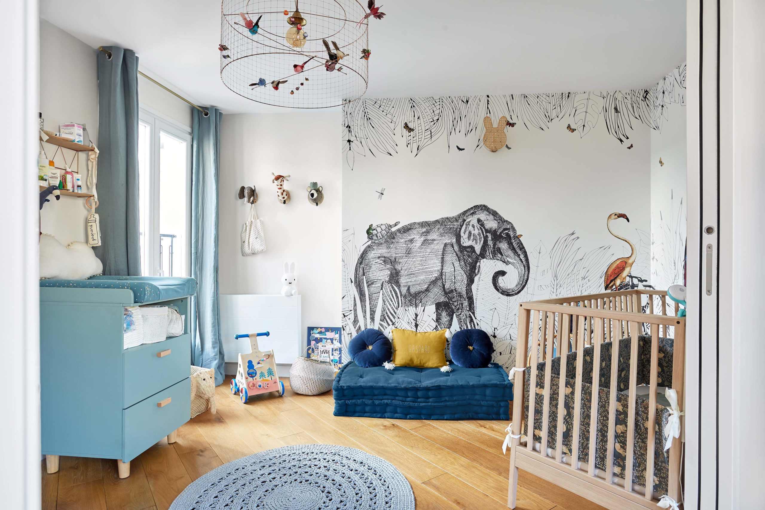 chambre bébé dans les tons bleu clair avec papier-peint panoramique murs et merveilles
