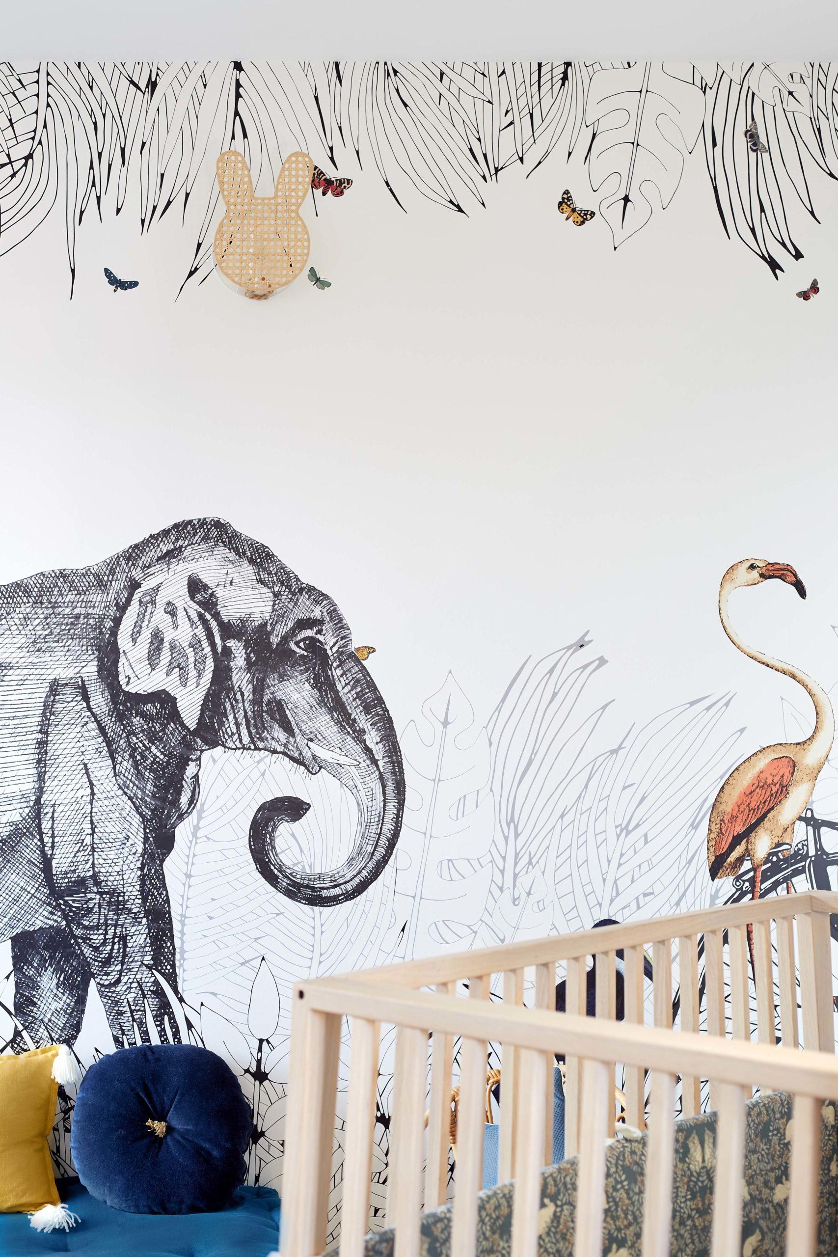 chambre bébé avec lit barreaux et papier-peint panoramique murs et merveilles