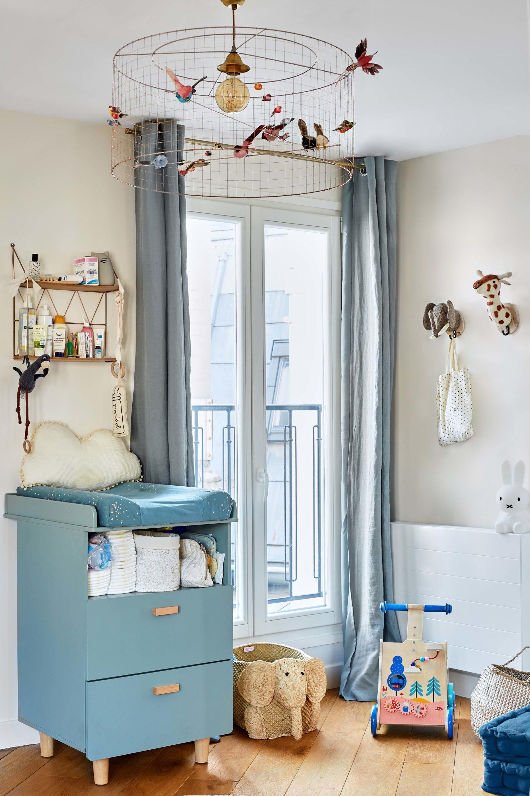 chambre bébé avec table a langer bleue et suspension oiseaux murs et merveilles